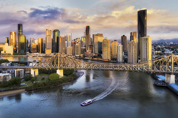 CLose to Story bridge across Brisbane river in front of Brisbane city CBD high-rise business and apartment towers with fast ferry on the water under the bridge.