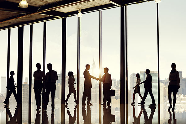 Silhouettes of business people walking, talking, and shaking hands with glass windows and a view of a cityscape in the background.